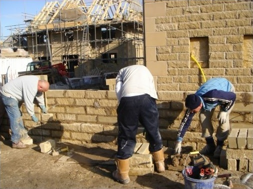 Bricklayers constructing stone boundary wall