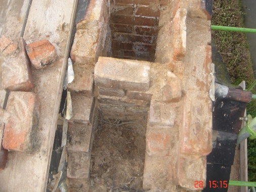 Stripped down chimney stack revealing a blocked chimney used as a bird nest